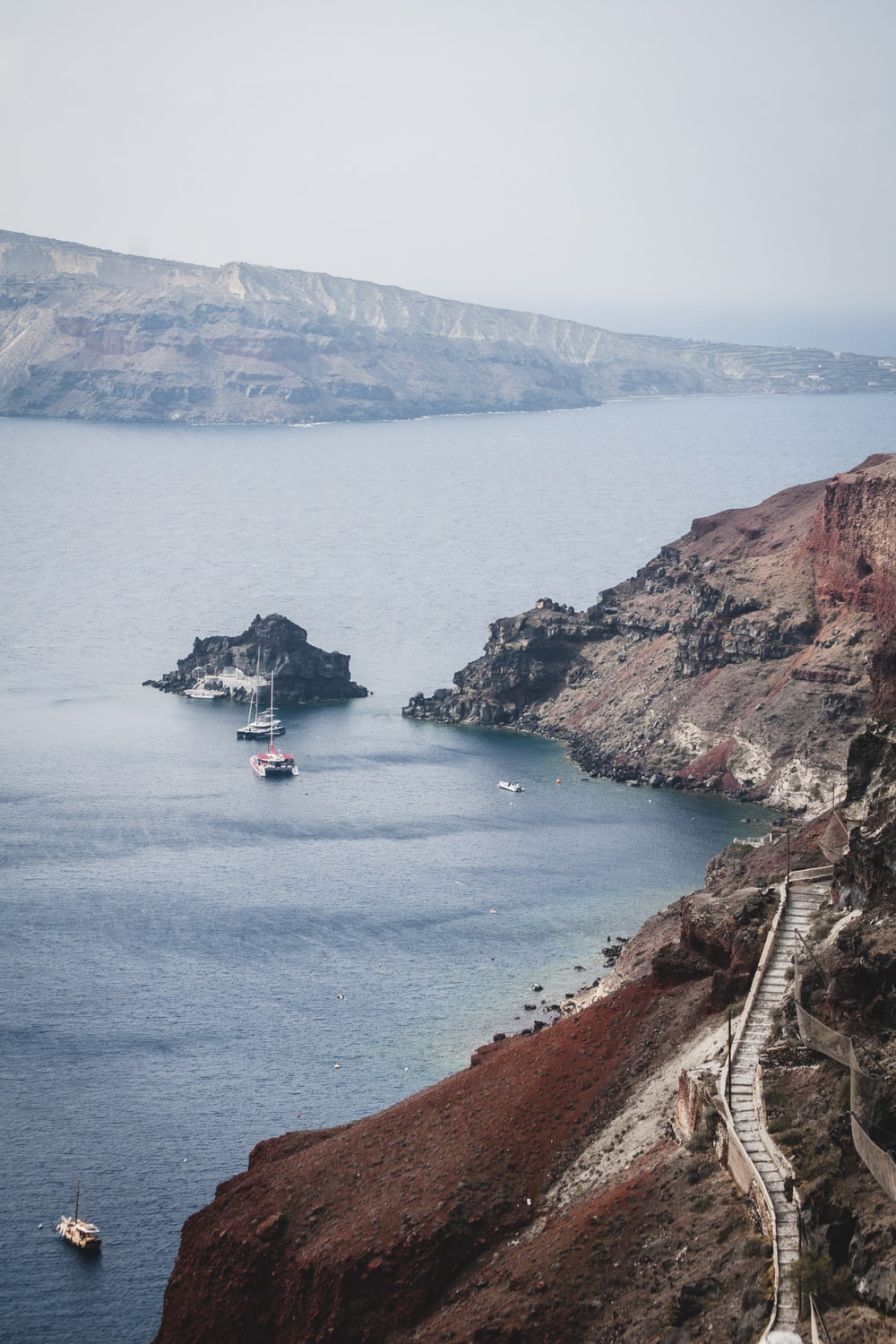 few boats on sea viewing cliff and mountain