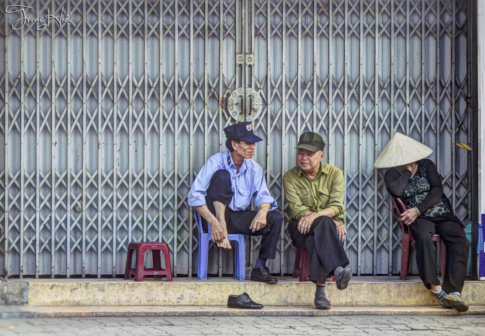 three person sitting on chairs beside gate