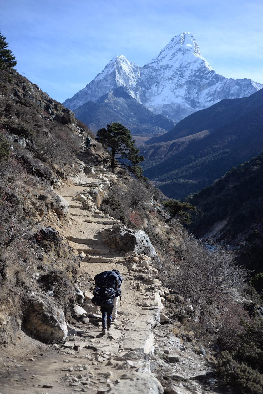 man wearing backpack climbing the mountain