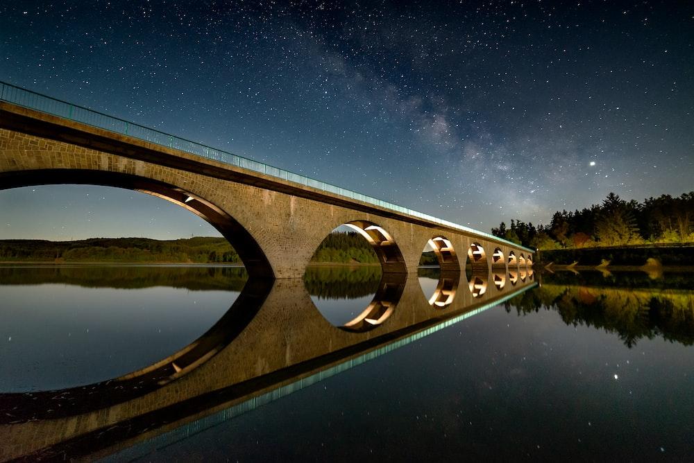 brown concrete bridge over water during night