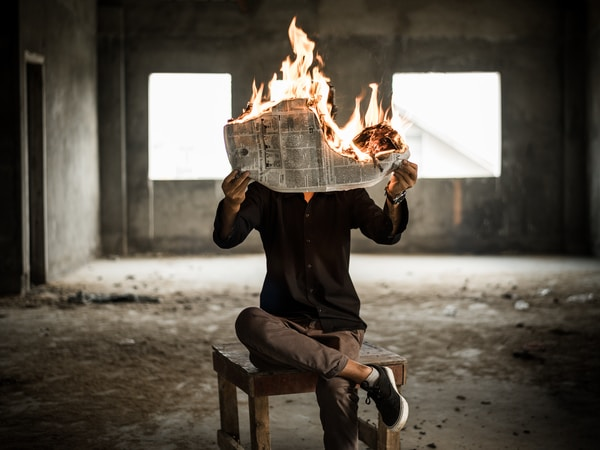 Weekly World News. man sitting on chair holding newspaper on fire