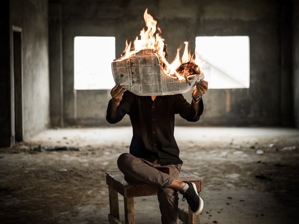 man sitting on chair holding newspaper on fire