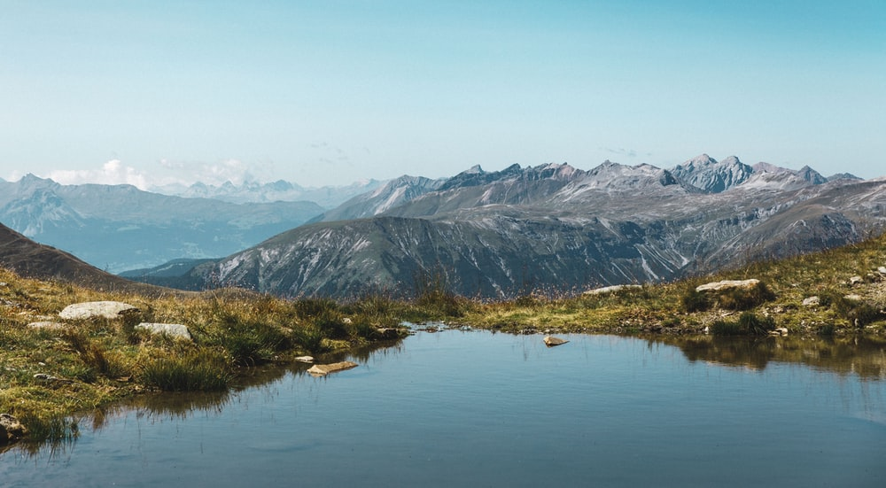body of water and mountains during day