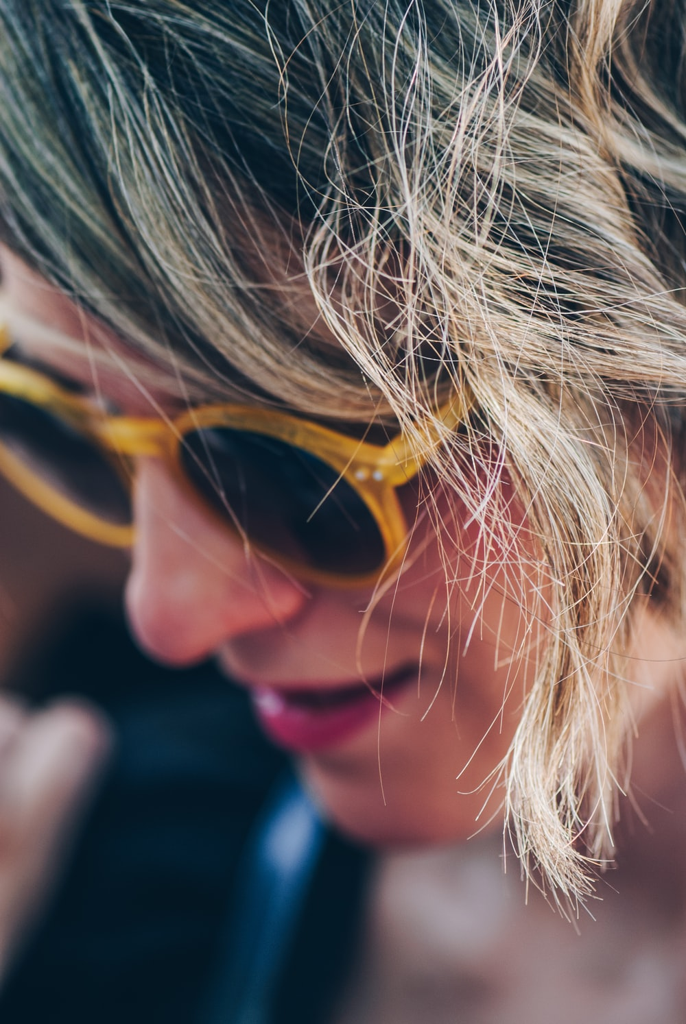 woman wearing yellow framed sunglasses looking down