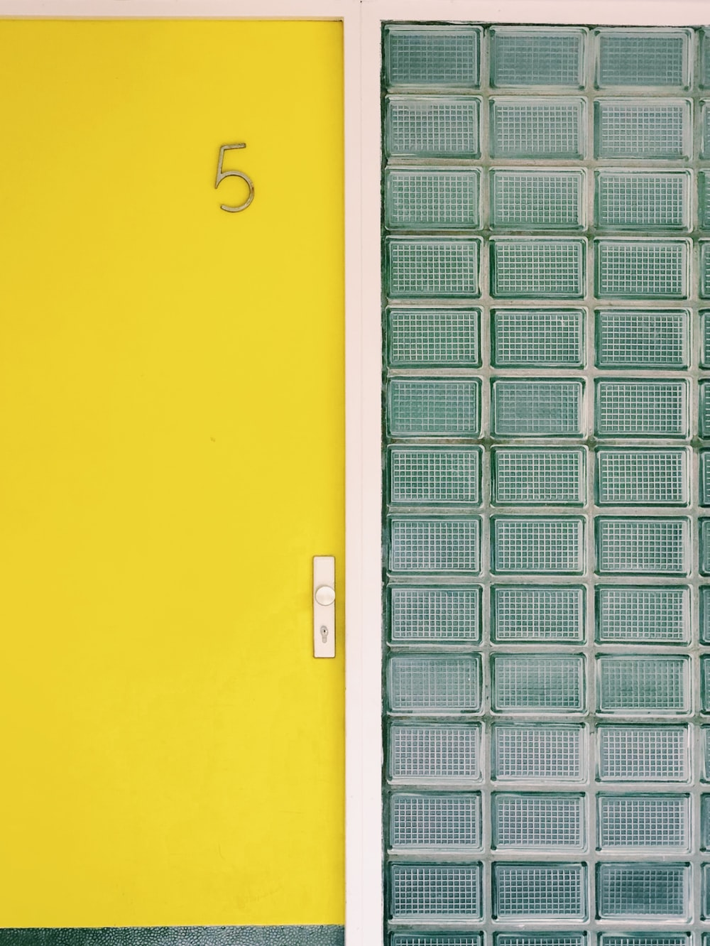 close yellow door by pressurized glass wall