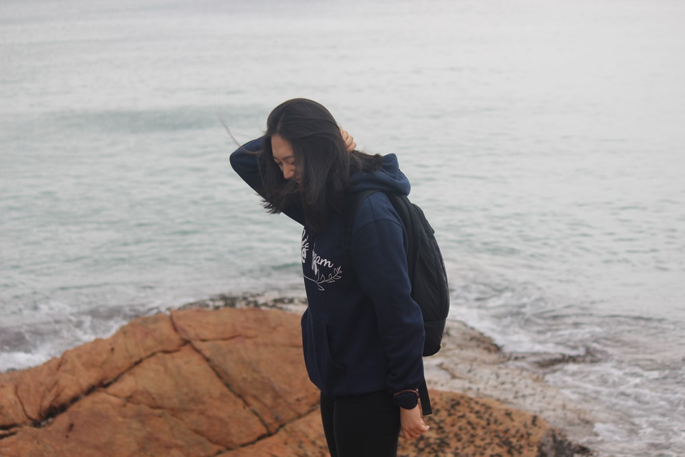 woman standing on brown rock viewing sea