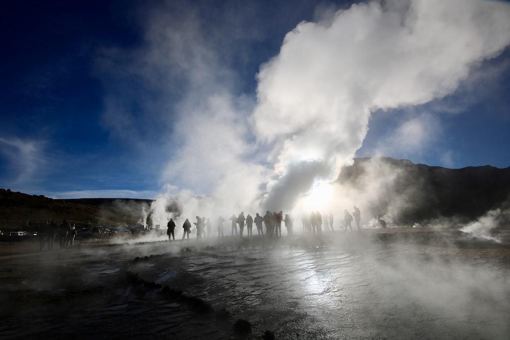 people surrounding a hot spring emitting smoke during golden hour