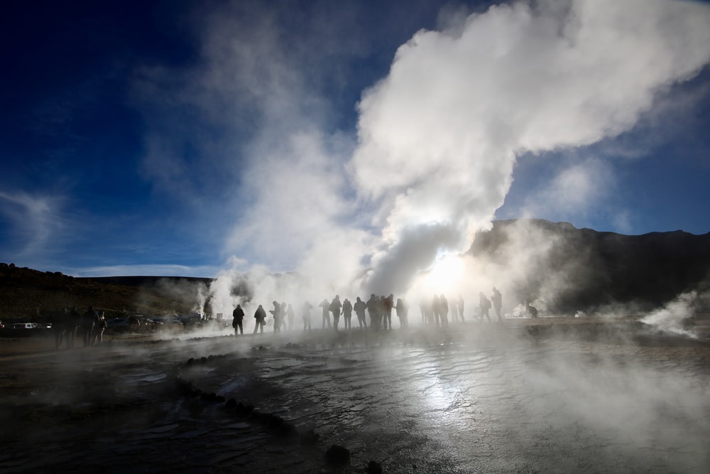 people surrounding a hot spring emitting smoke during golden hour