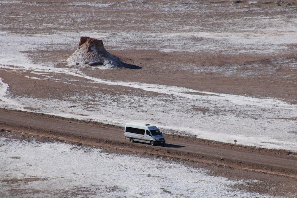 white passenger van travelling on road across desert