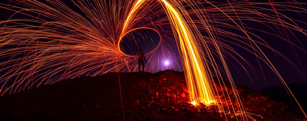 person on top of hill steel wool photography