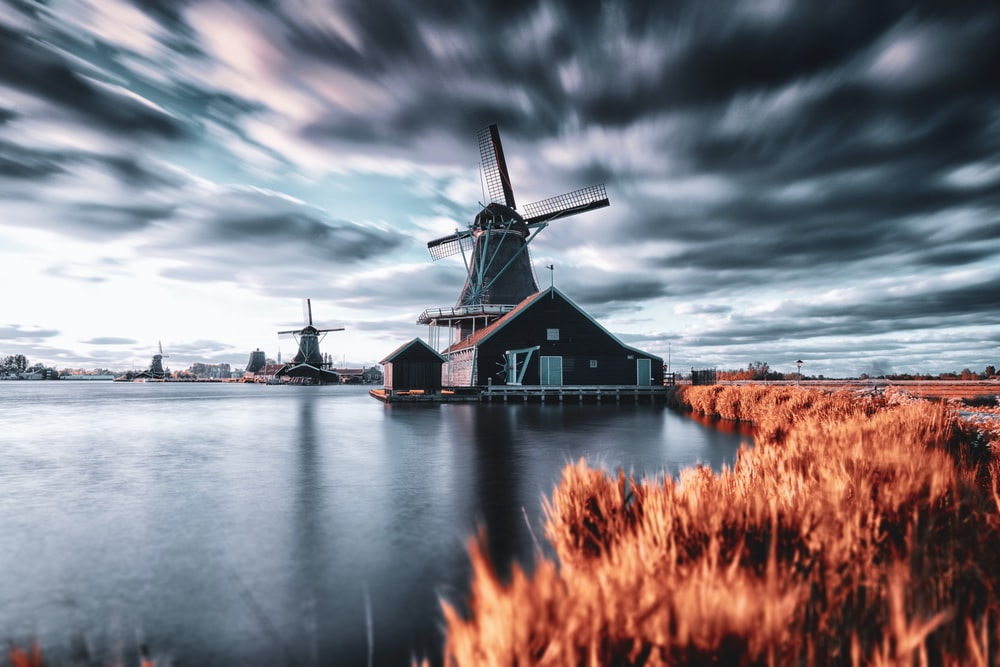windmill house beside body of water during day