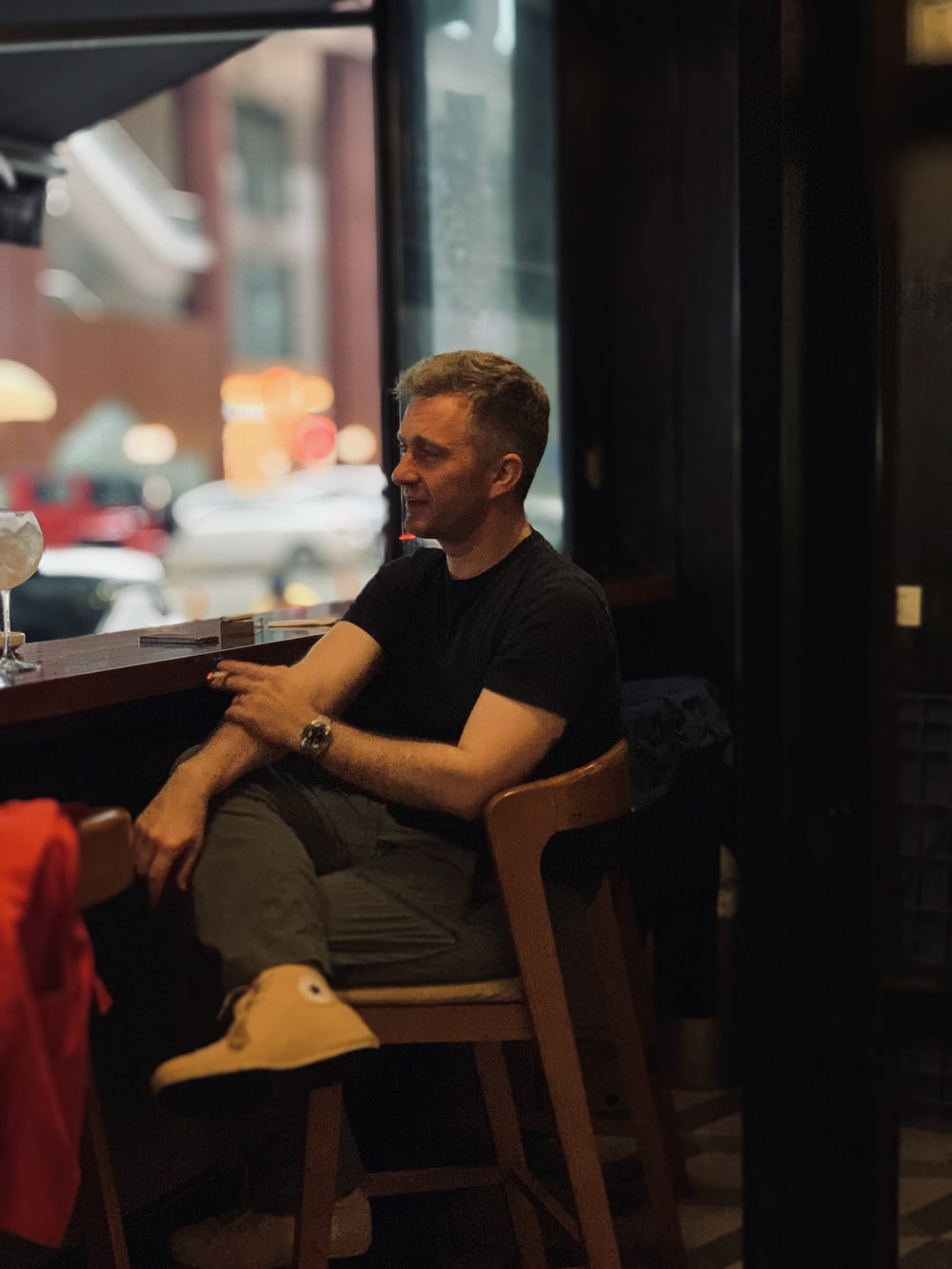 man sitting on bar chair beside counter
