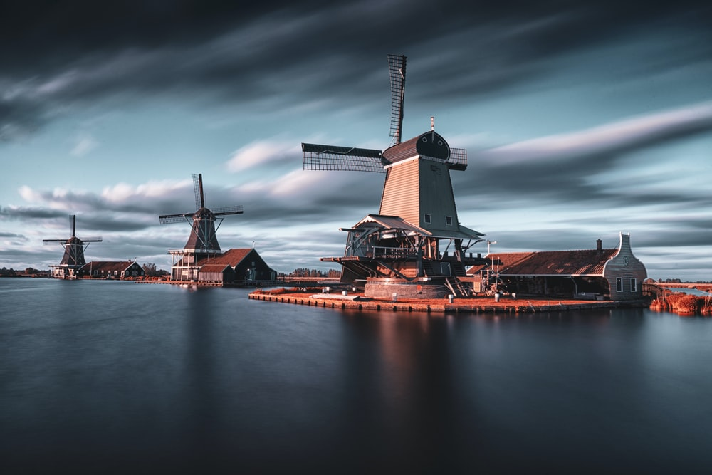 three windmills by the lake under grey cloudy sky