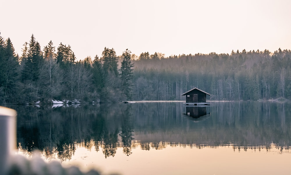 black and grey wooden boat house floating in glassy lake