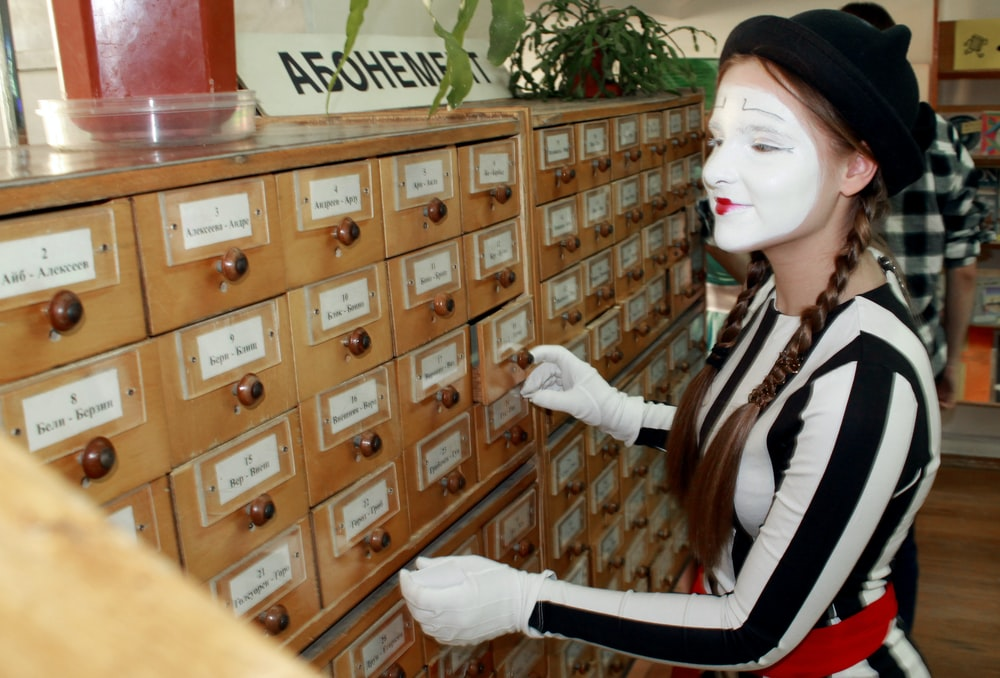 female mime by a wooden drawers