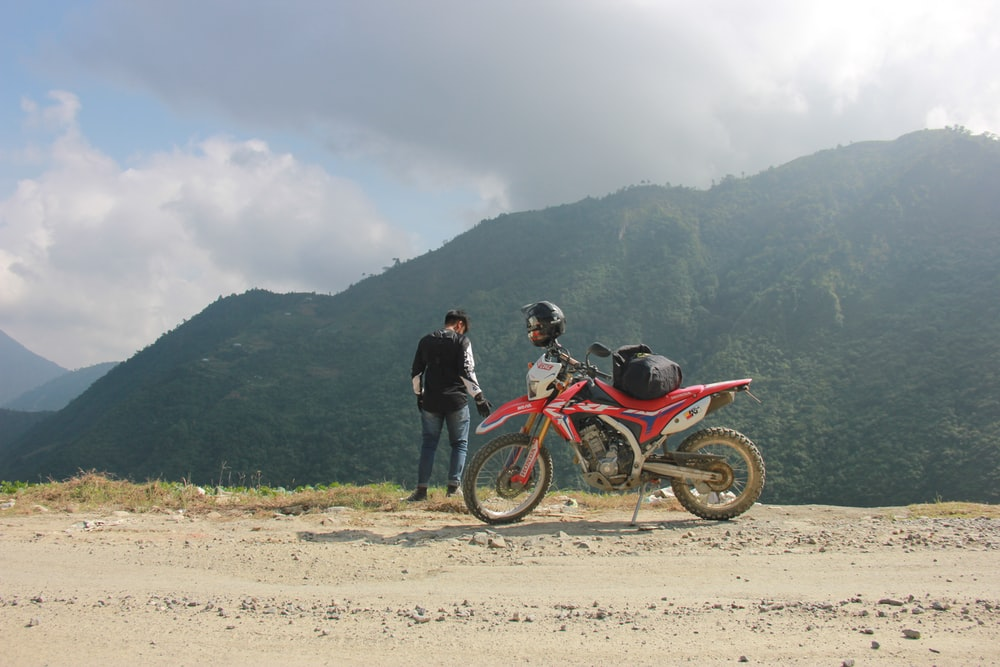 man standing near motocross dirt bike