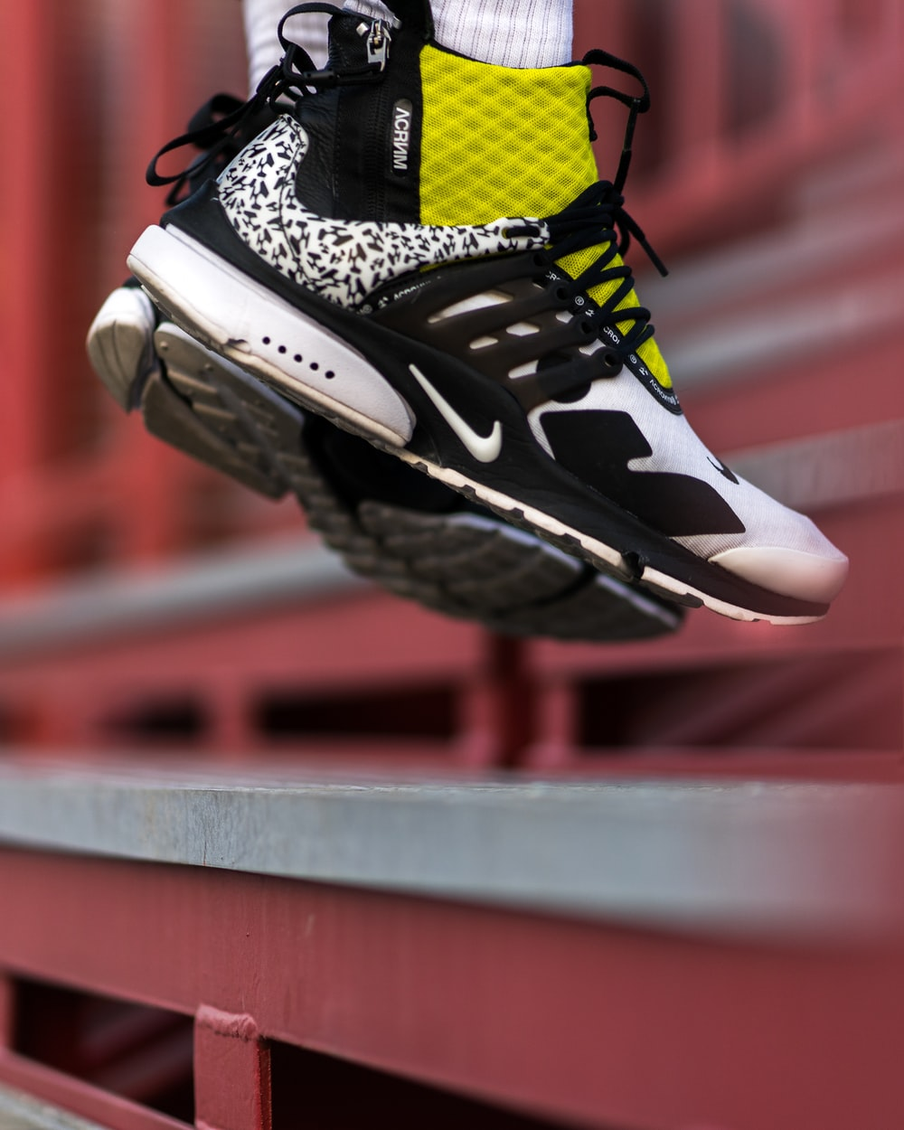 pair of white, black and yellow Nike shoes