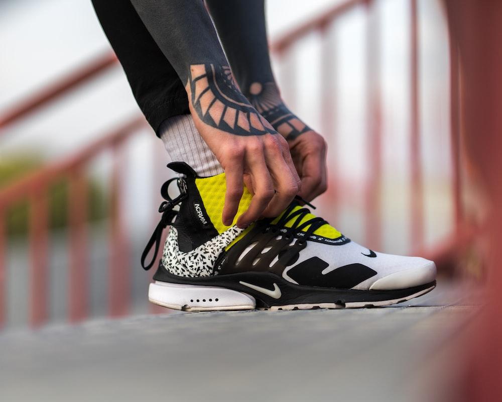unpaired white, black, and yellow Nike shoe