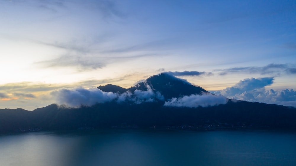 silhouette photography of mountain surrounded with clouds