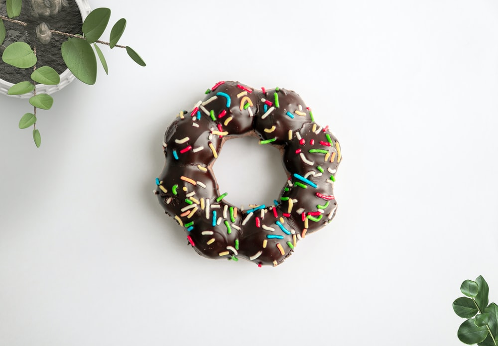 doughnut coated with chocolate with candy sprinkles toppings