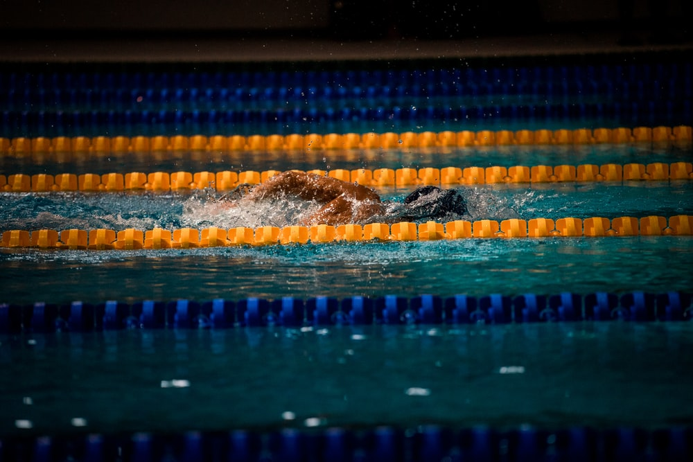 man swimming in pool with lane ropes