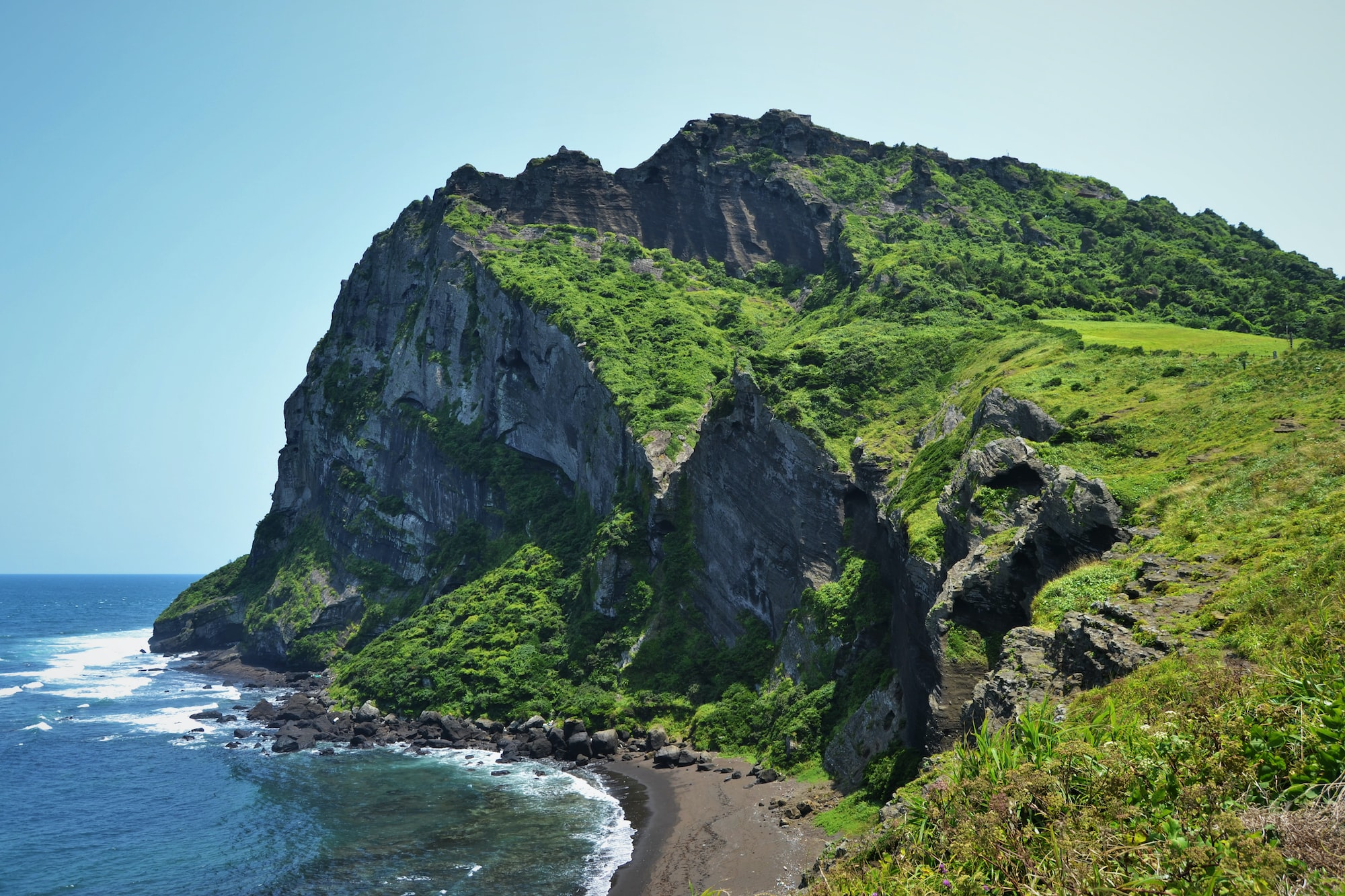 This picture showcases Seongsan Ilchulbong in Jeju Island, South Korea. The picture shows a still volcano from the inland, with a volcanic black beach and lush greenery; a place stripped of all human life. A gigantic cliff crashes into the sea and creates a gorgeous interplay between sky, land, and seaside. The waves crash onto the side of the cliff and the sky is completely clear, with no obstructions and no clouds. A beautiful, sunny day in Jeju Island, the biggest volcanic island of South Korea. The countryside and the scenery inspire adventure in this amazing natural park full of beauty.