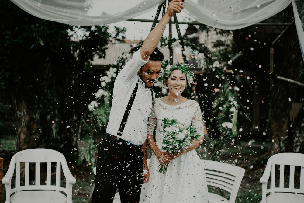 man raising his right arm beside woman holding bouquet of flowers