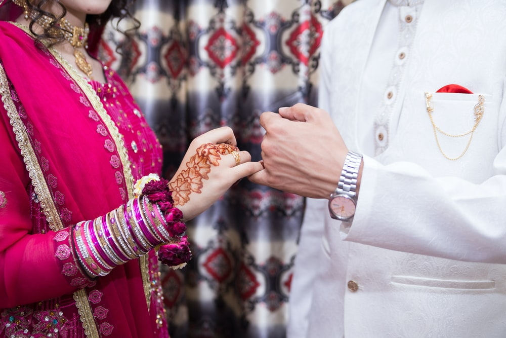 a man and a woman with linked pinky fingers