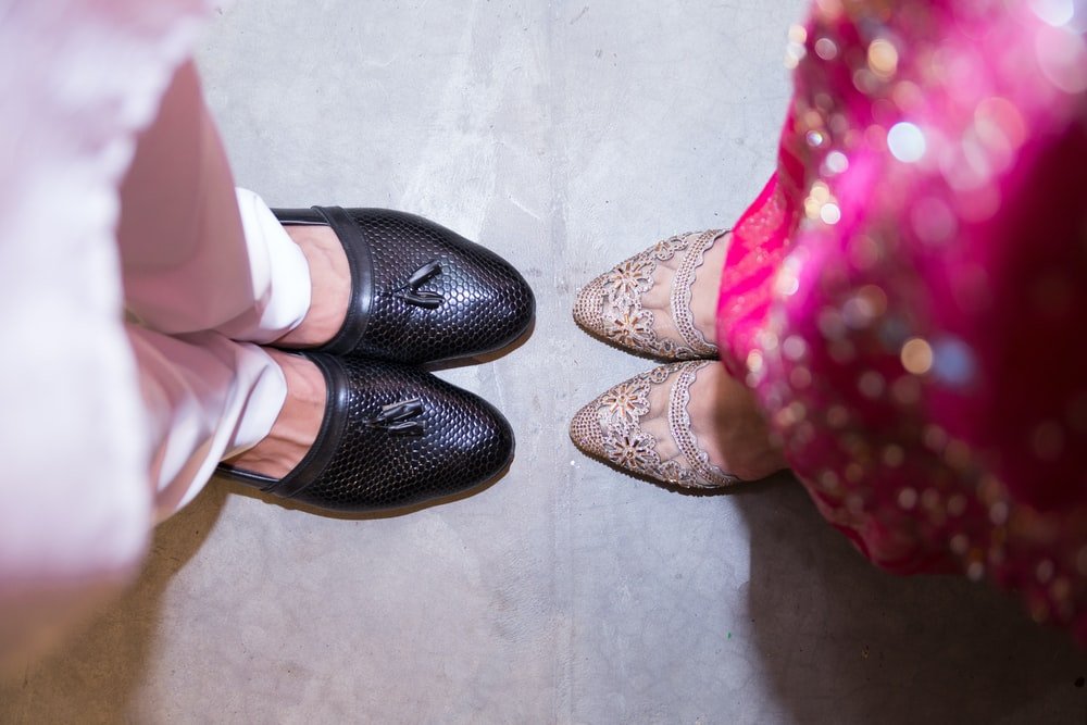 two women wearing black and white shoes