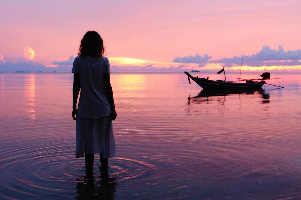 woman and a boat at sea