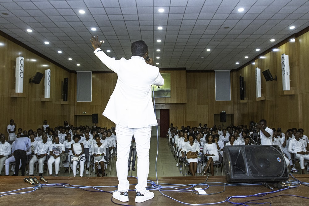 man standing on stage in front of people