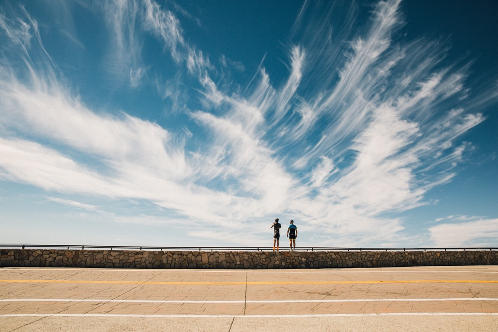two persons standing on handrail during day