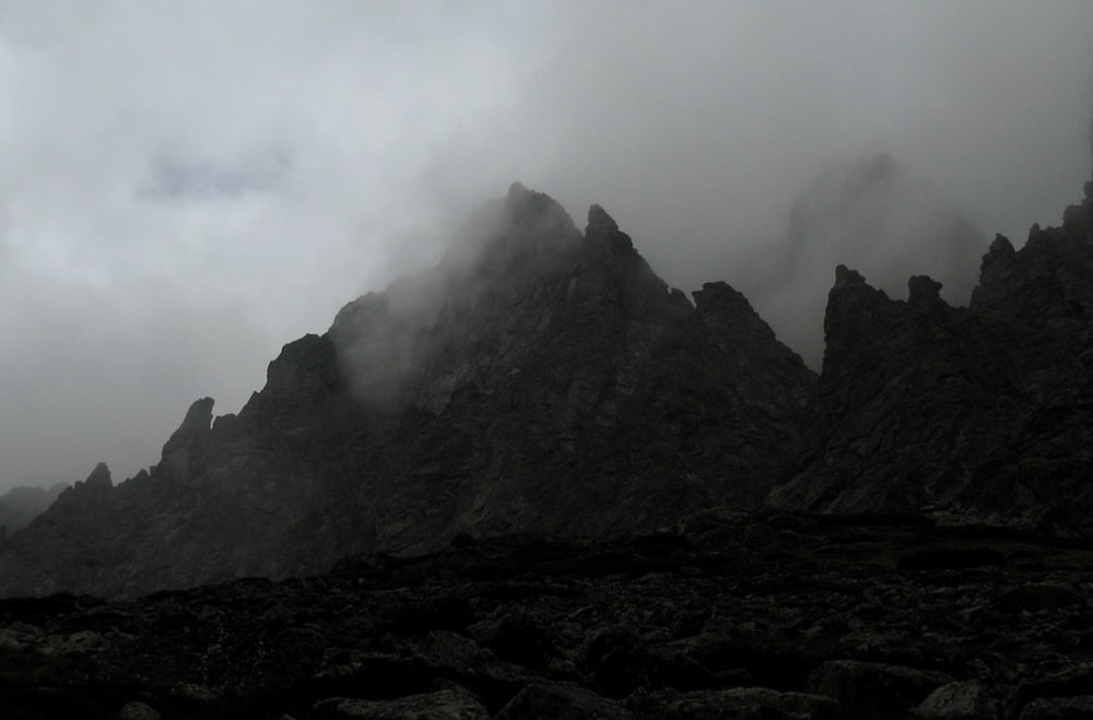 grayscale photo of a foggy mountain