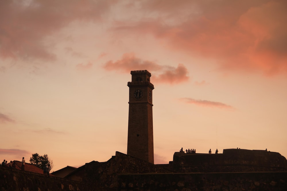 grey and pink cloudy sunset sky over tower