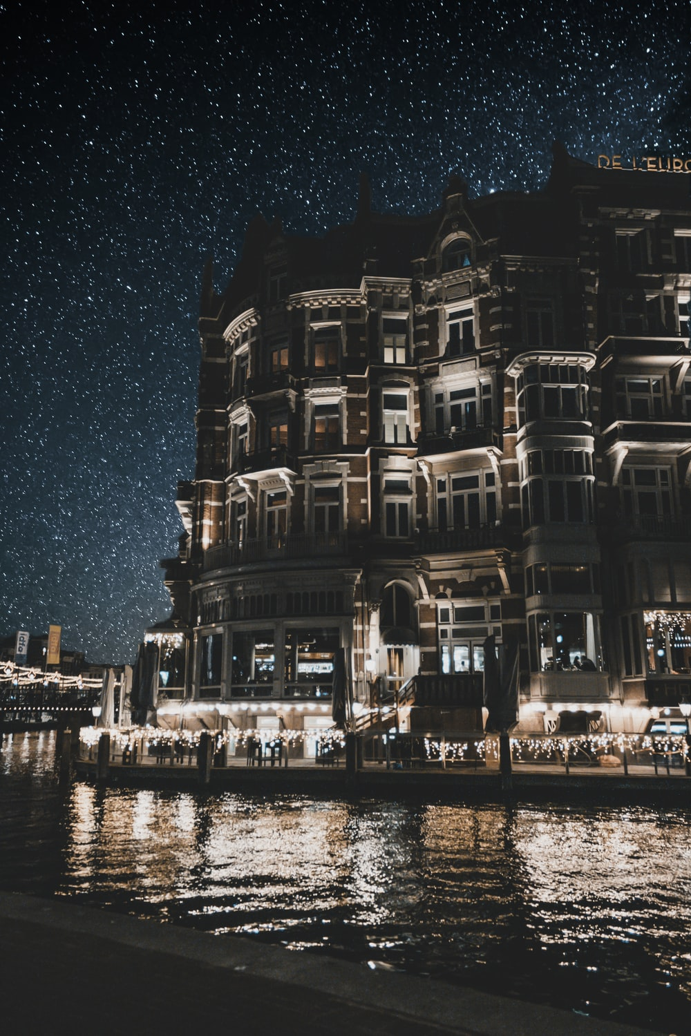 starry night sky over store building along the river