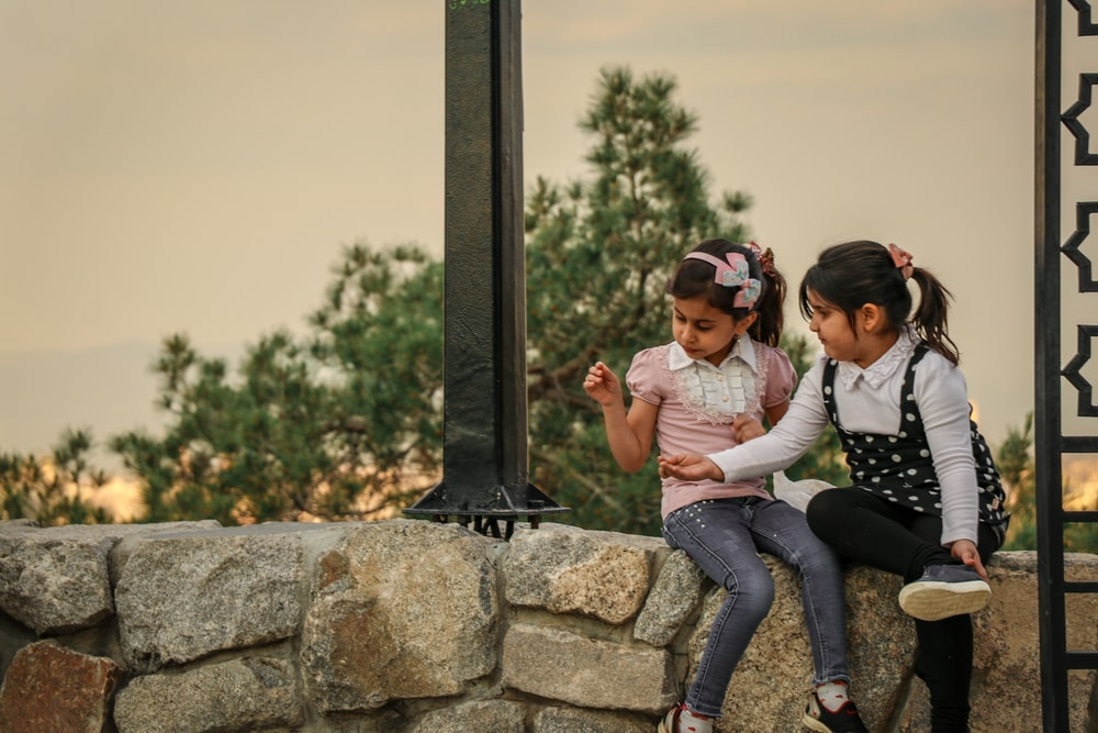 two girls seated on a rock wall