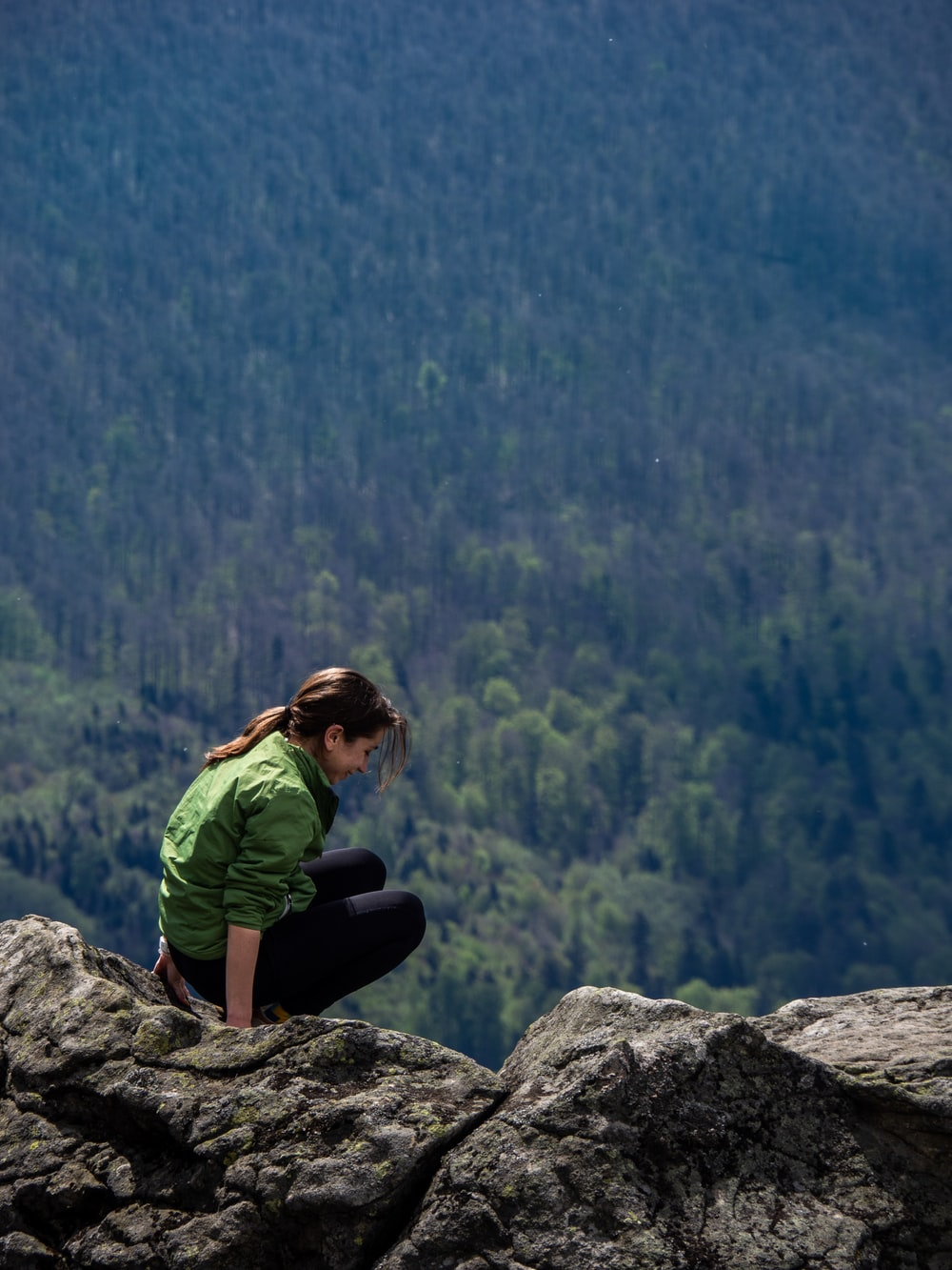 woman sitting on rocky mountain near the forest