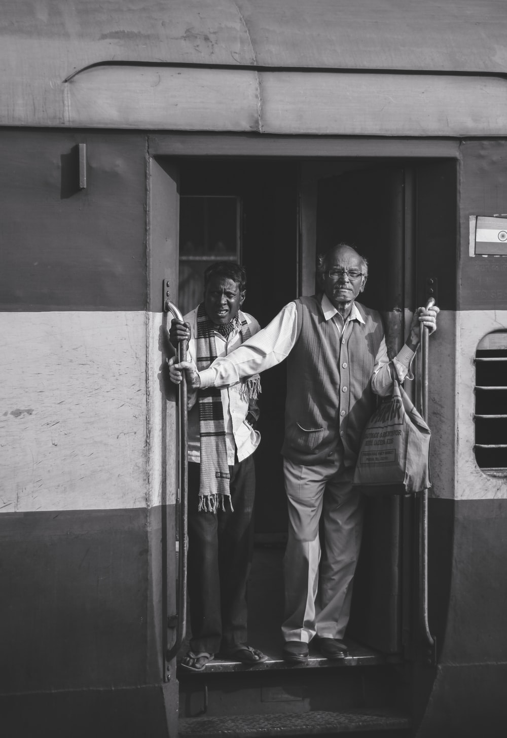 two men standing on the doorway of a train
