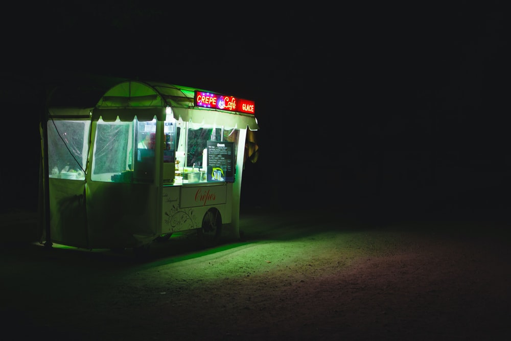 food cart with lights on during nighttime