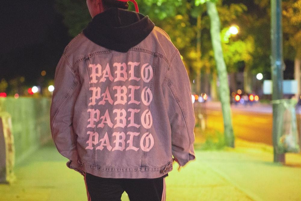 man wearing jacket standing on sidewalk