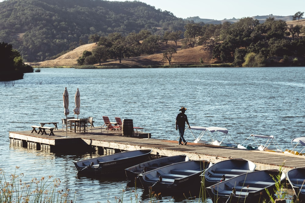 man walking on dock with boats during daytime