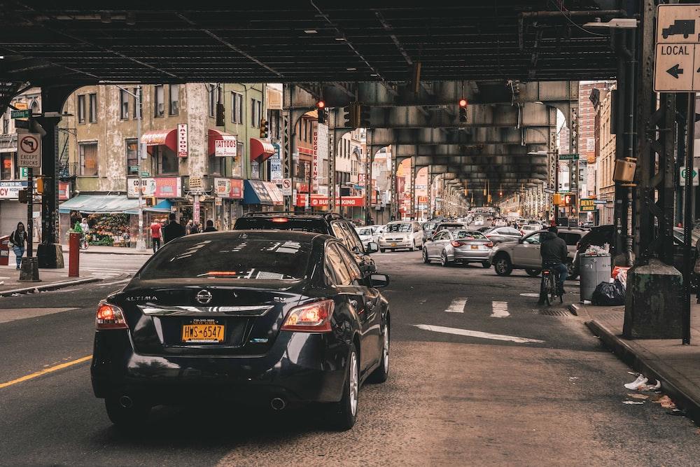 vehicles on the road under bridge near buildings