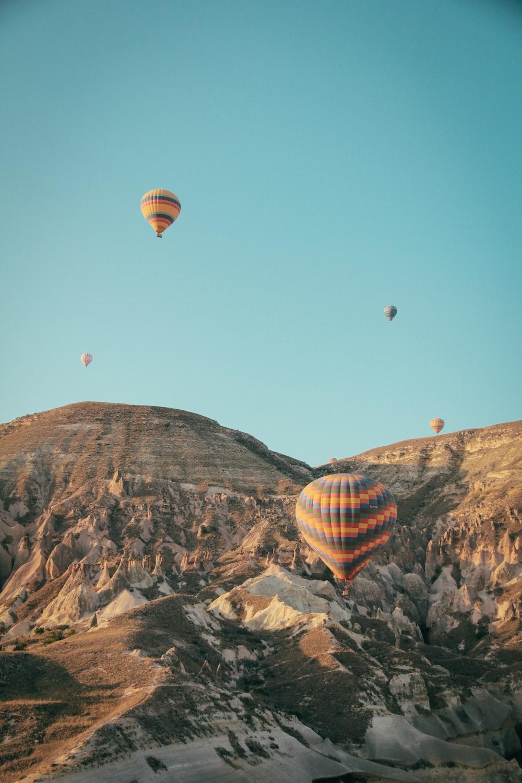 hot air balloons over rocky mountains