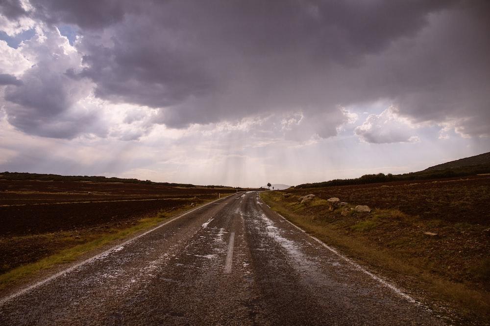 empty road between fields under cloudy sky