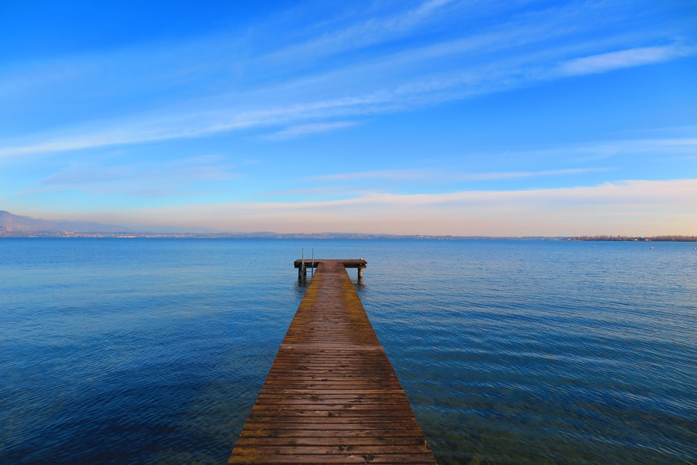 brown wooden dock on body of water under blue sky