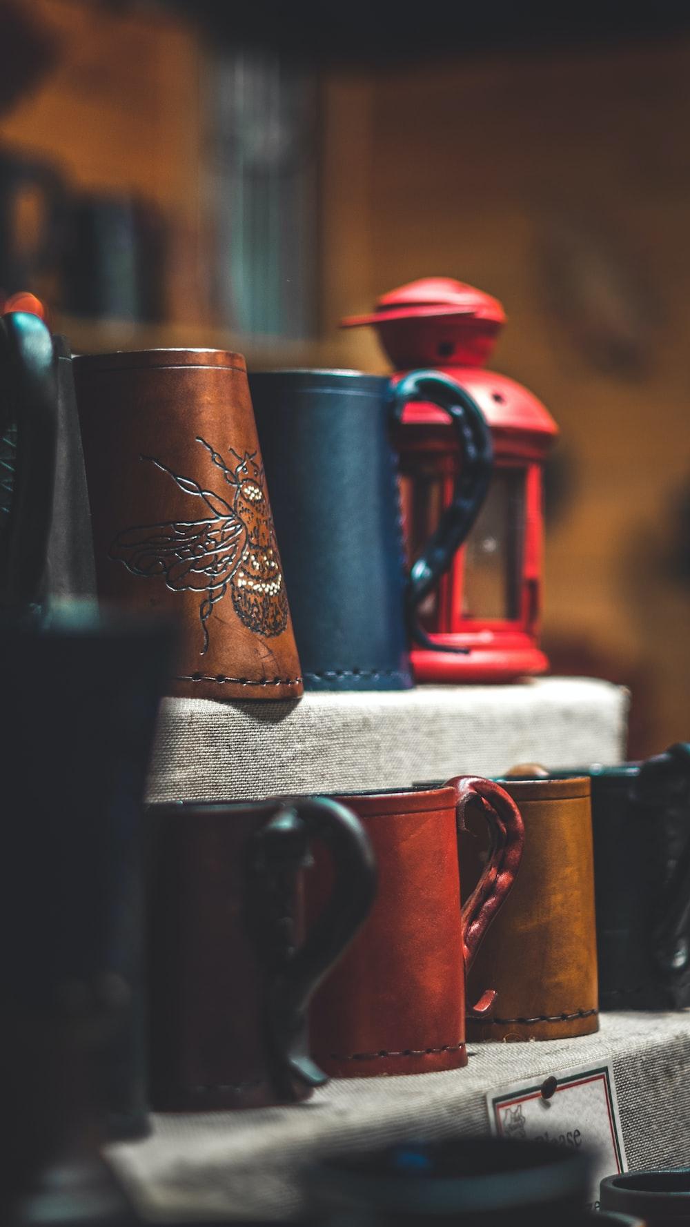brown and black mugs on rack