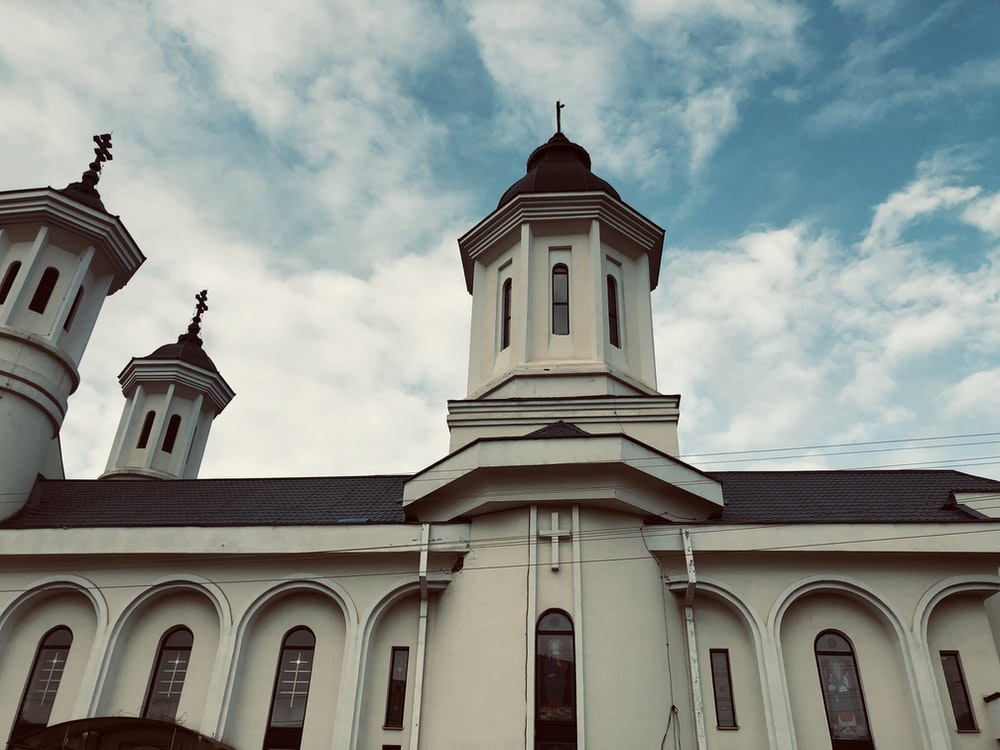 white and black cathedral under cloudy sky