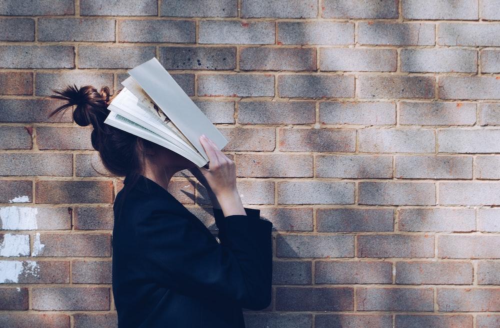 白い本で彼女の顔を覆っている女性