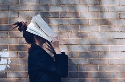 woman covering her face with white book study zoom background
