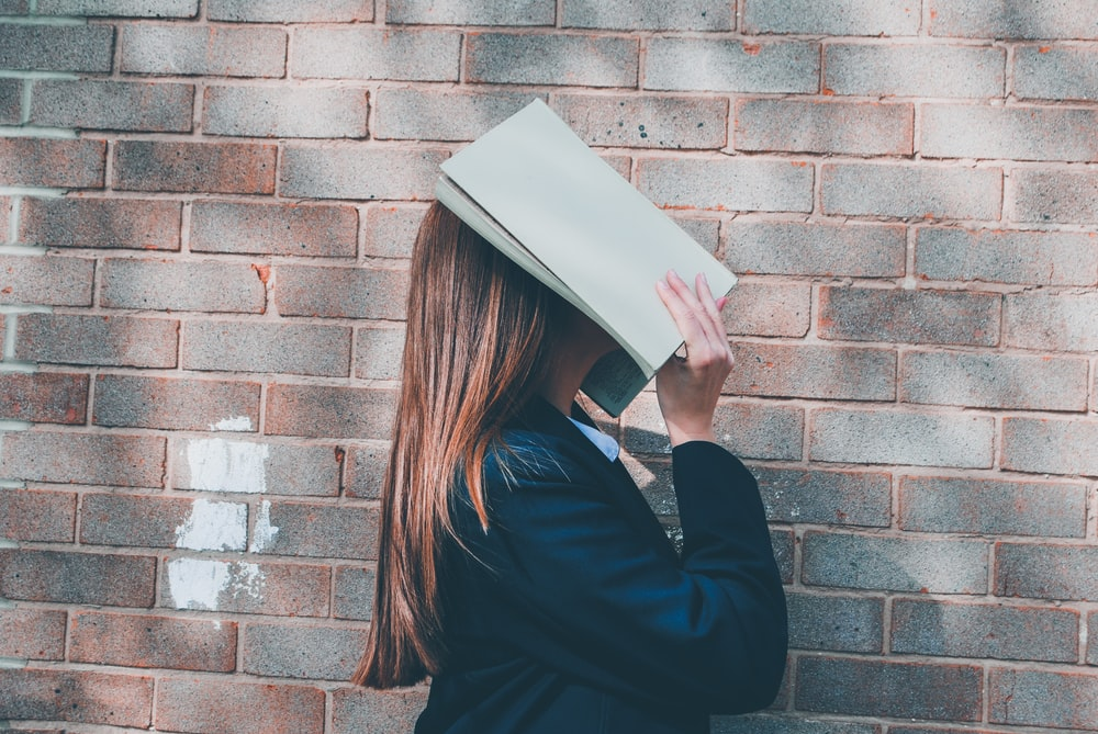 woman covering her face with an open book
